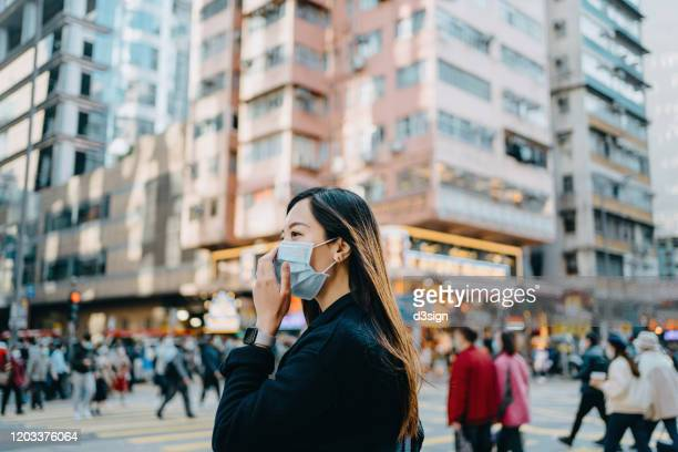 asian woman with protective face mask crossing road in downtown city street against crowd of pedestrians and highrise urban buildings - viral infection stock pictures, royalty-free photos & images