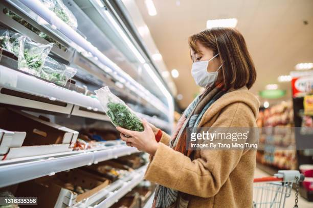 asian woman with protective face mask doing grocery shopping for fresh vegetable in supermarket - supermarket stock pictures, royalty-free photos & images