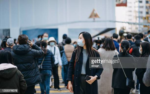 asian woman with protective face mask holding smartphone standing in the middle of busy downtown city street amidst crowd of pedestrians passing by - epidemic imagens e fotografias de stock