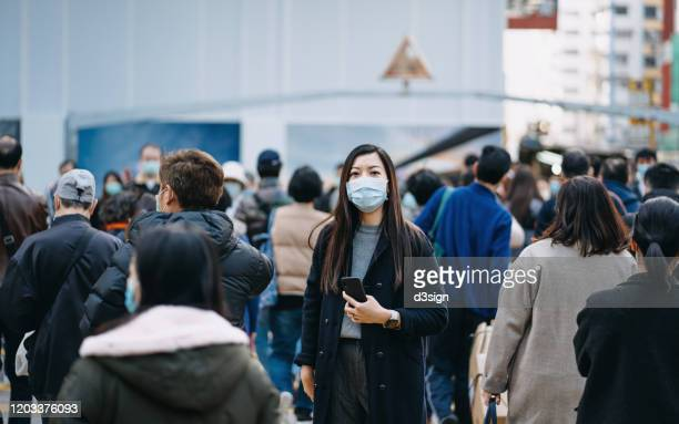 asian woman with protective face mask holding smartphone standing in the middle of busy downtown city street amidst crowd of pedestrians passing by - epidemi bildbanksfoton och bilder