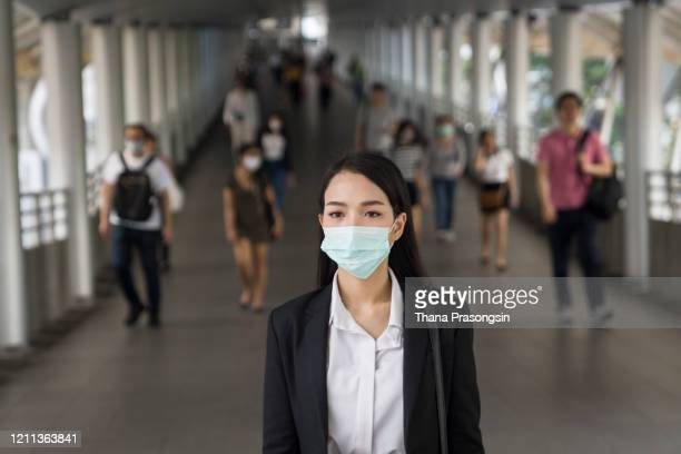 asian woman with protective face mask in the urban bridge in city against crowd of people - stress coronavirus stock pictures, royalty-free photos & images