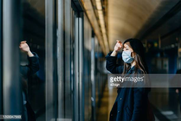 asian woman with protective face mask shielding eyes with her hand while commuting in the city and waiting for subway in platform - transport stock pictures, royalty-free photos & images