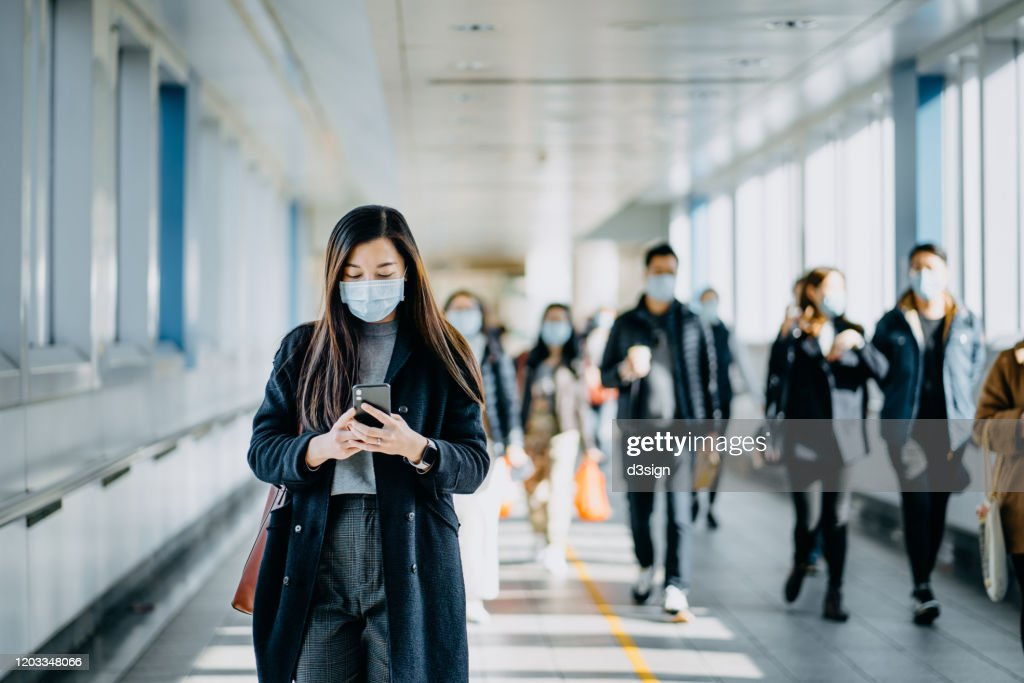 Asian woman with protective face mask using smartphone while commuting in the urban bridge in city against crowd of people : Stock Photo