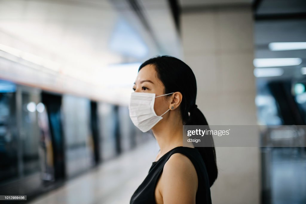 Asian woman with protective face mask waiting for subway MTR train in platform : Foto de stock