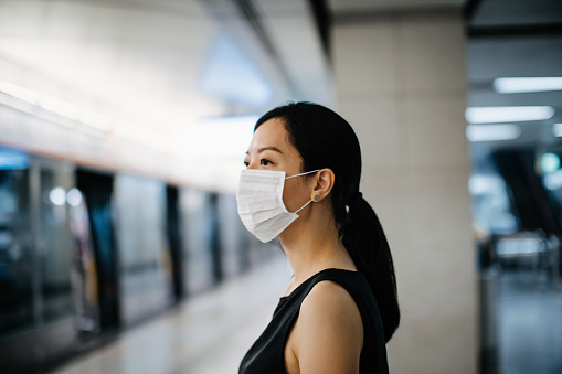 Asian woman with protective face mask waiting for subway MTR train in platform - gettyimageskorea