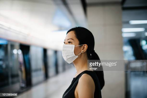asian woman with protective face mask waiting for subway mtr train in platform - epidemie stock-fotos und bilder