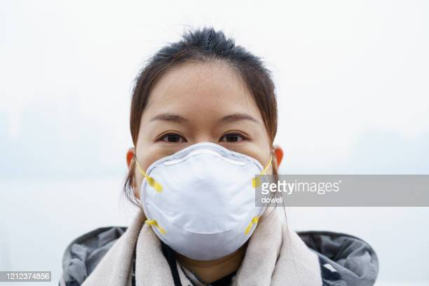 asian woman with protective n95 face mask - n95 face mask stock pictures, royalty-free photos & images