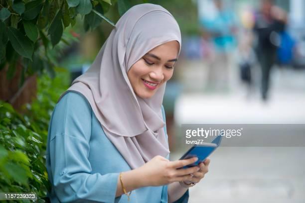 スマートフォンを持つアジアの女性 - 宗教的なベール ストックフォトと画像