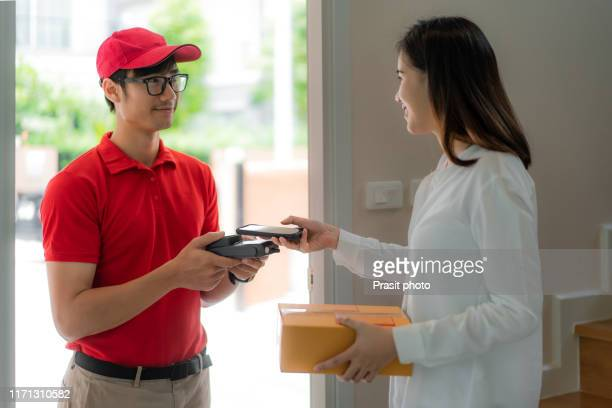 asian woman with smartphone using qr application for delivery payment with she receive the customer box at home. - send ストックフォトと画像