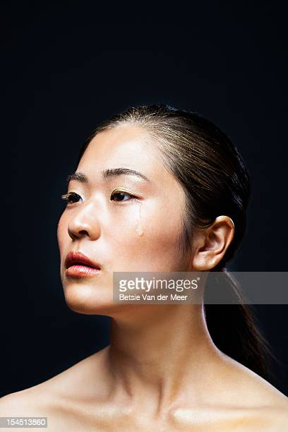Asian woman with tear rolling down on cheek.