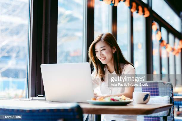 asian woman working laptop at cafe. - korea stock pictures, royalty-free photos & images