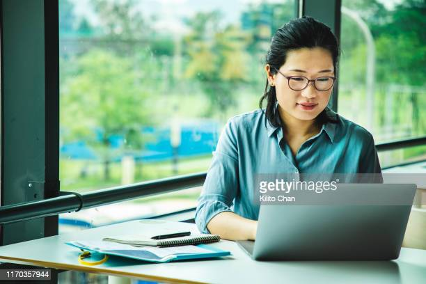 asian woman working on a laptop - human body part stock pictures, royalty-free photos & images