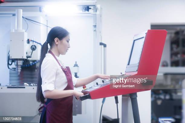 asian woman working on machinery in technical office - sigrid gombert stock pictures, royalty-free photos & images