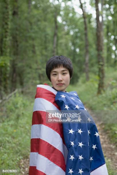 asian woman wrapped in american flag in forest - démocratie photos et images de collection