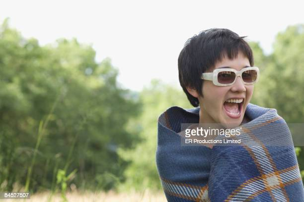 asian woman wrapped in blanket wearing trendy sunglasses - aveyron photos et images de collection