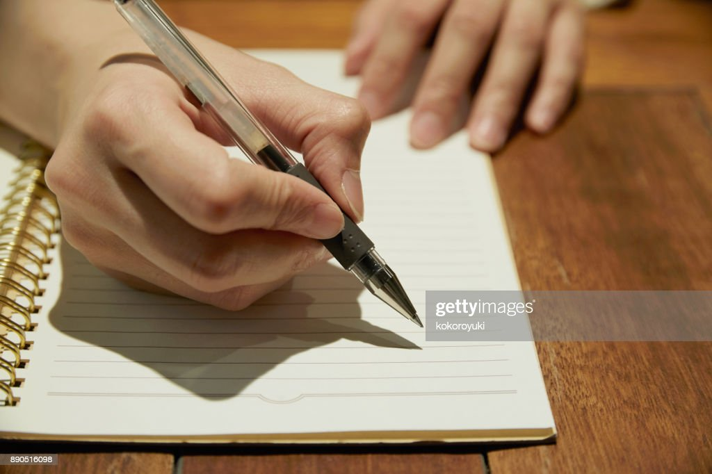 Asian woman writing on the book : Stock Photo
