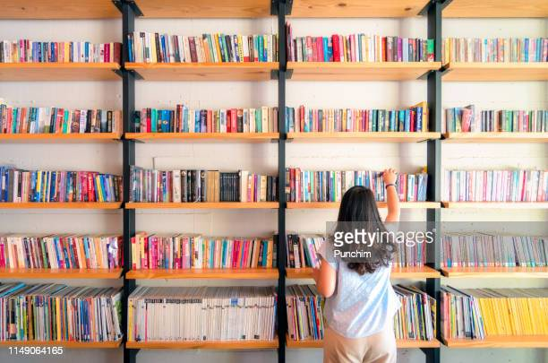 asian women are picking up books on the bookshelf. to prepare to back to school - reading stock pictures, royalty-free photos & images