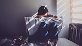 Asian women are sitting hugging their knees in bed. Feeling sad, disappointed in love In the dark bedroom and sunlight from the window through the blinds.Vintage tone.