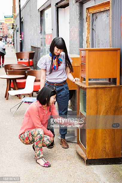 Asian women checking out an old tv at market shop.