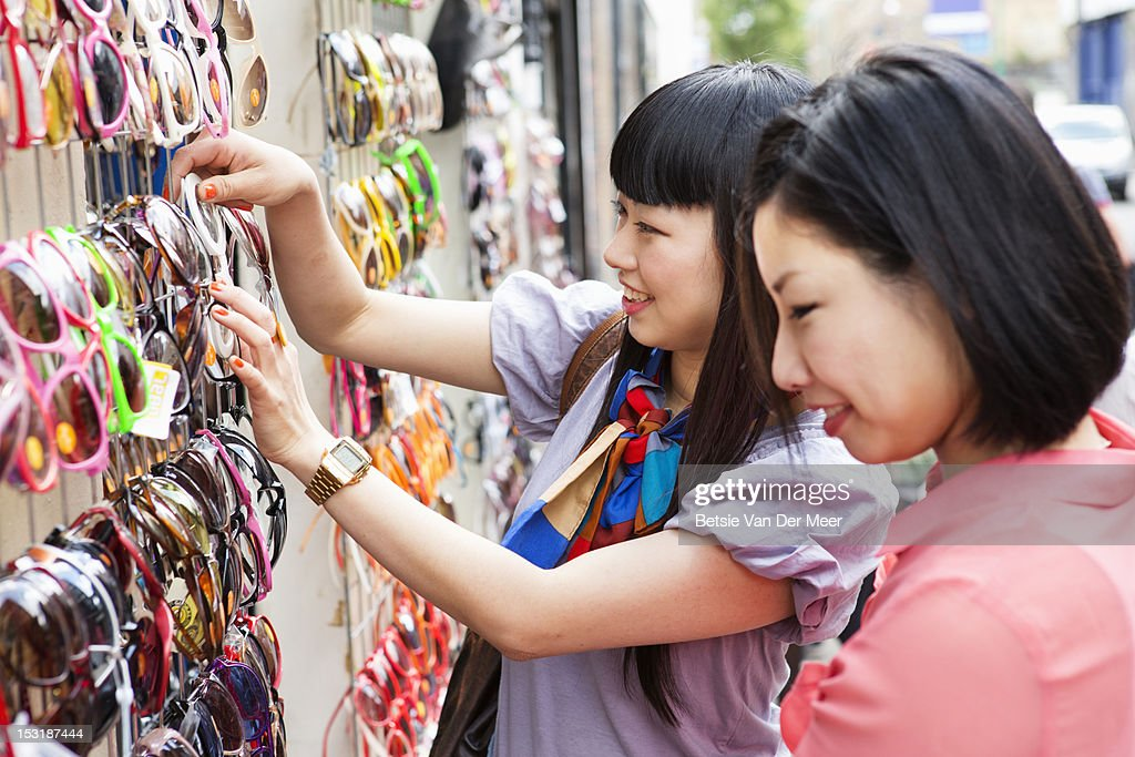 Asian women choosing sunglasses at market stall. : ストックフォト