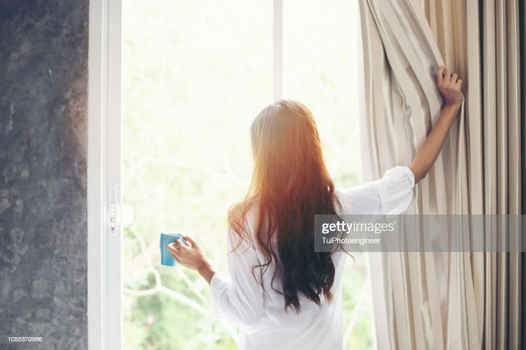 Asian women drinking coffee and wake up in her bed fully rested and open the curtains in the morning to get fresh air on sunshine : Stock Photo