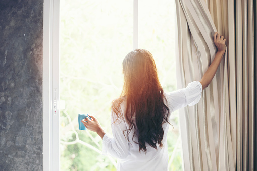 Asian women drinking coffee and wake up in her bed fully rested and open the curtains in the morning to get fresh air on sunshine 1055370966