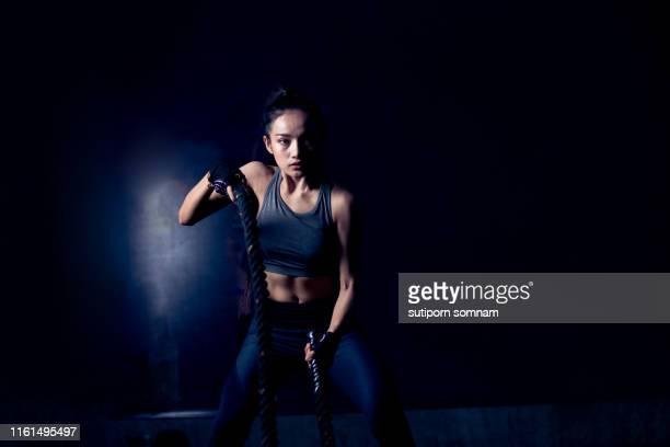 asian women exercise workout in gym fitness breaking with battle rope - combat sport stockfoto's en -beelden