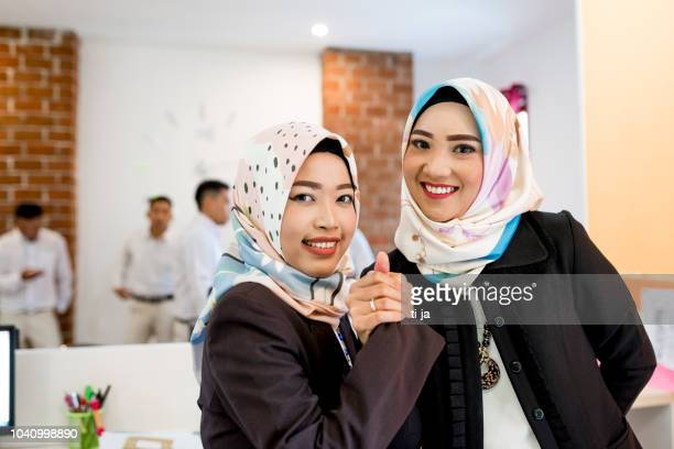 asian women holding hands at office - indonesia stock pictures, royalty-free photos & images