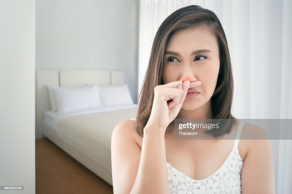 Asian women in white dress feeling unwell and sneeze at bedroom. : Stock Photo
