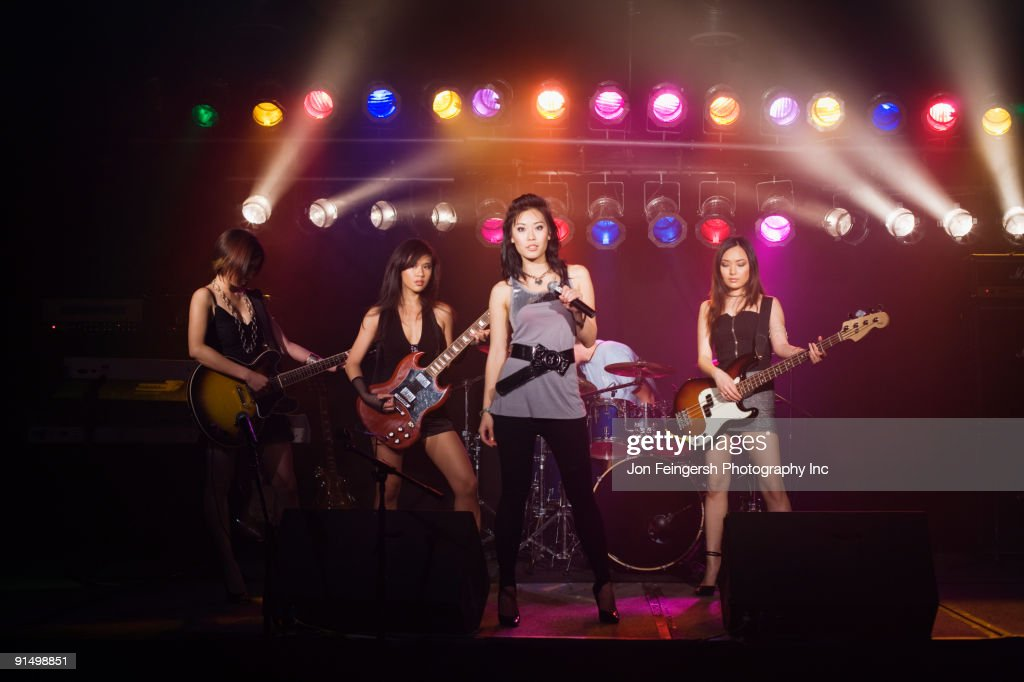 Asian women singing and playing electric guitar onstage : Stock Photo