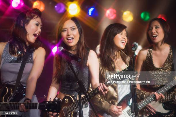 asian women singing and playing electric guitar onstage - girl band stock pictures, royalty-free photos & images