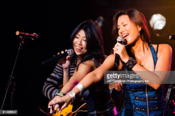 asian women singing and pointing onstage - pop musician stock pictures, royalty-free photos & images