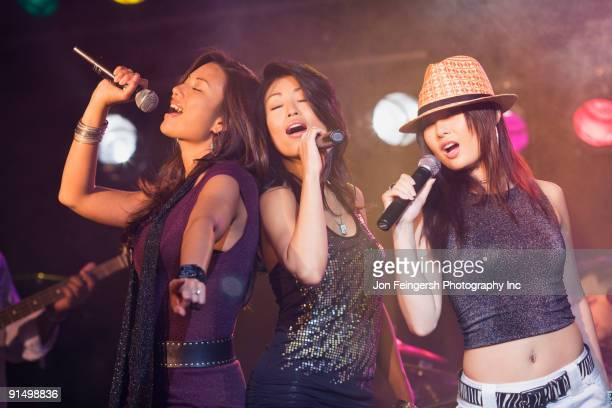 Asian women singing onstage
