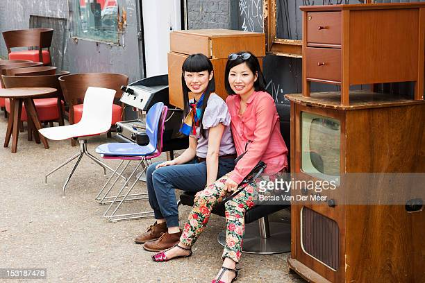 2 asian women sitting on chair at market shop.