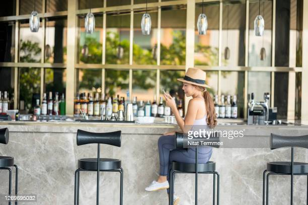 asian women tourist ordering drink and text messaging in luxury hotel bar counter. - incidental people stock pictures, royalty-free photos & images