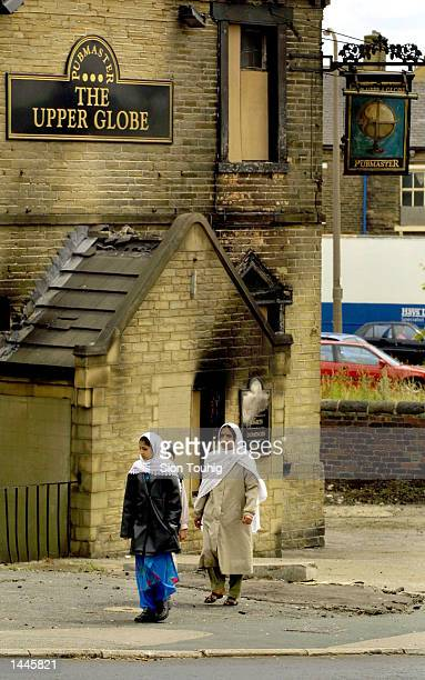 Asian women walk around the Manningham District of Bradford July 14 2001 in England The neighborhood has been the site of recent rioting caused by...