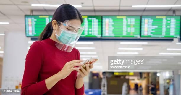 アジアの女性は、飛行機で旅行するときに身を守るためにマスクと顔の隠れ女を着用します。 - フェイスシールド ストックフォトと画像