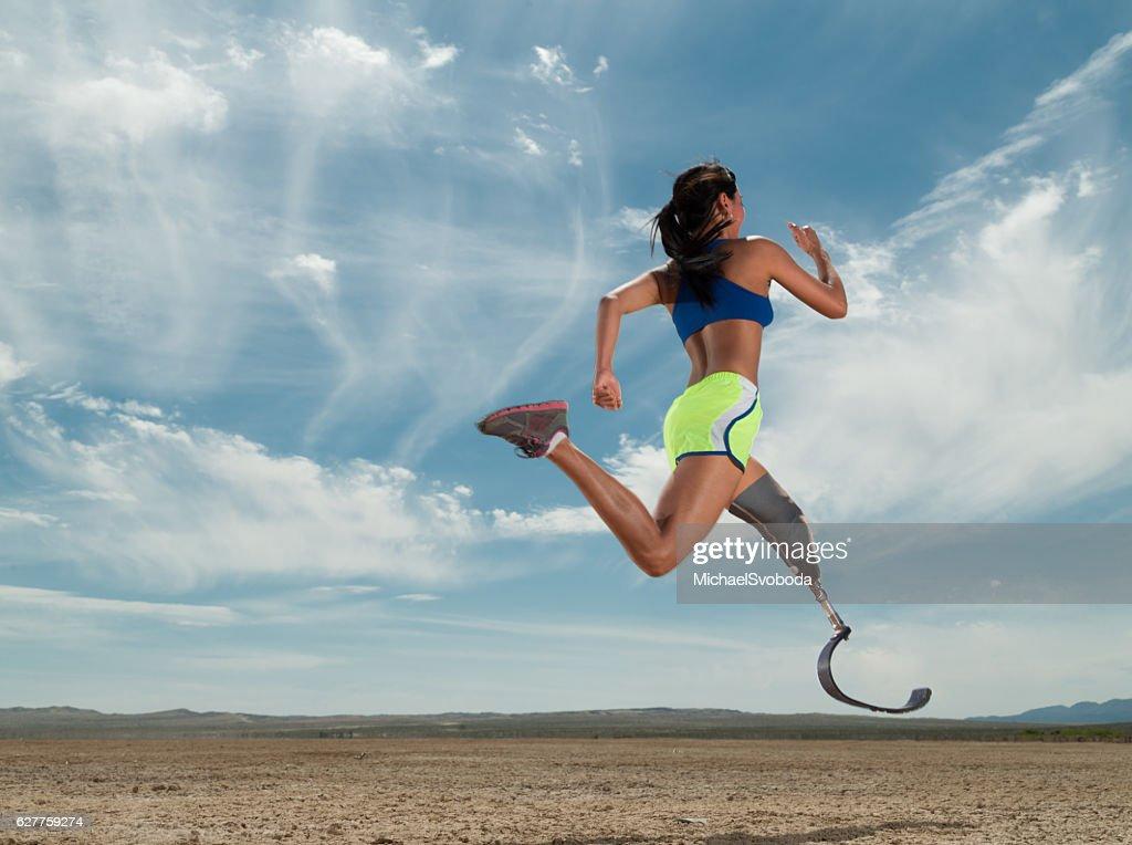 Asian Women With Prosthetic Leg Running In The Desert : Stock Photo
