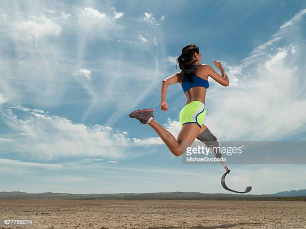 asian women with prosthetic leg running in the desert - amputiert stock-fotos und bilder