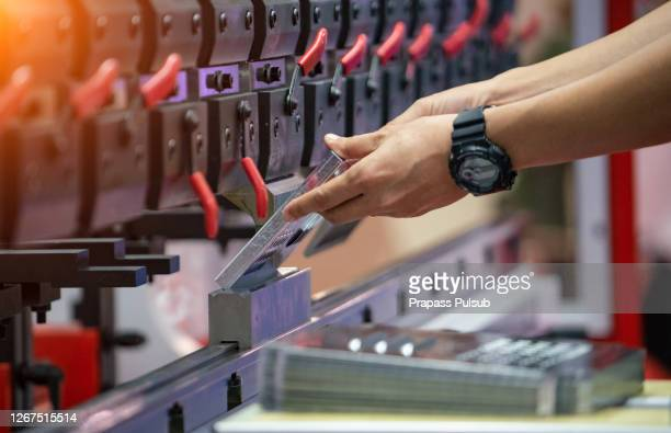 asian worker in factory at metal skip machine putting work - fabricage apparatuur stock pictures, royalty-free photos & images