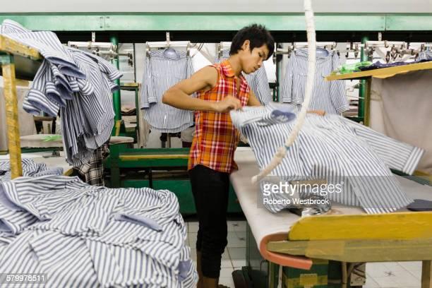 Asian worker ironing shirt in garment factory