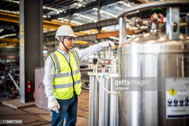 asian worker operating a gas tank in a factory - flammable stock photos and pictures