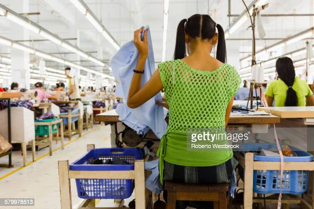 asian worker sewing clothing in garment factory - top garment stockfoto's en -beelden