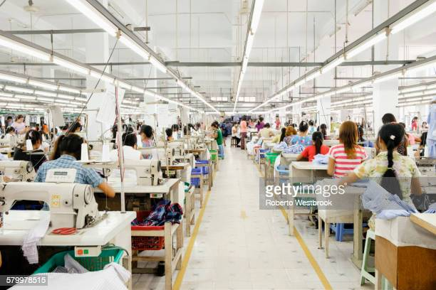 asian worker sewing clothing in garment factory - 織物工場 ストックフォトと画像