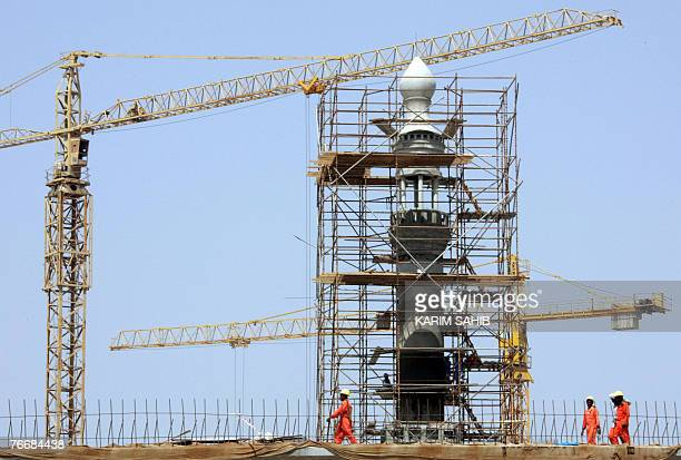 Asian workers are seen at the construction site of a new mosque ahead of the holy fasting month of Ramadan 12 September 2007 Across much of the...