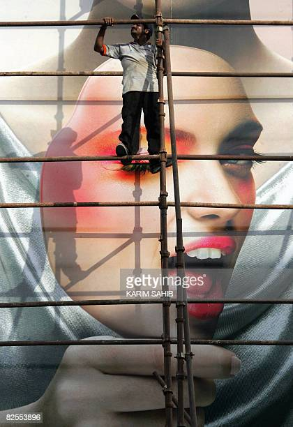 Asian workers climb on scaffolding as they change a huge advertising poster on a billboard in the Gulf emirate of Dubai on August 24 2008 As the...