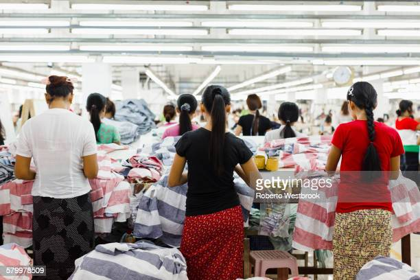Asian workers sewing clothing in garment factory