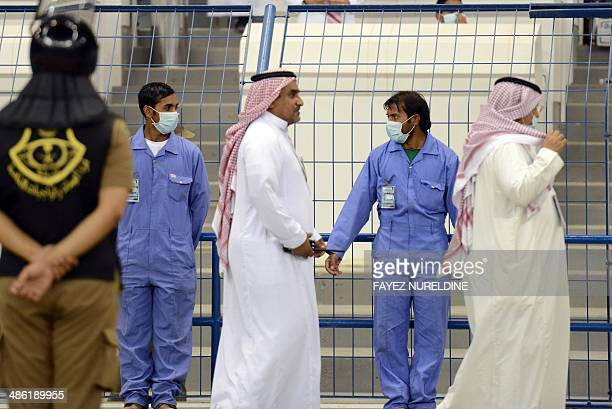 Asian workers wear mouth and nose masks while on duty during a football match at the King Fahad stadium on April 22 2014 in Riyadh The health...
