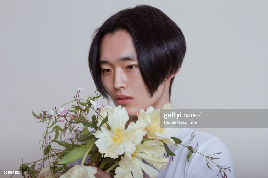 Asian young adult male holding and smelling bouquet of flowers : Stock Photo
