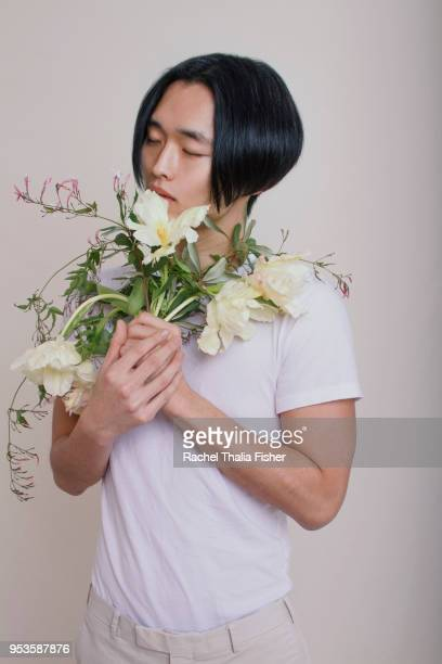 Asian young adult male holding and smelling bouquet of flowers